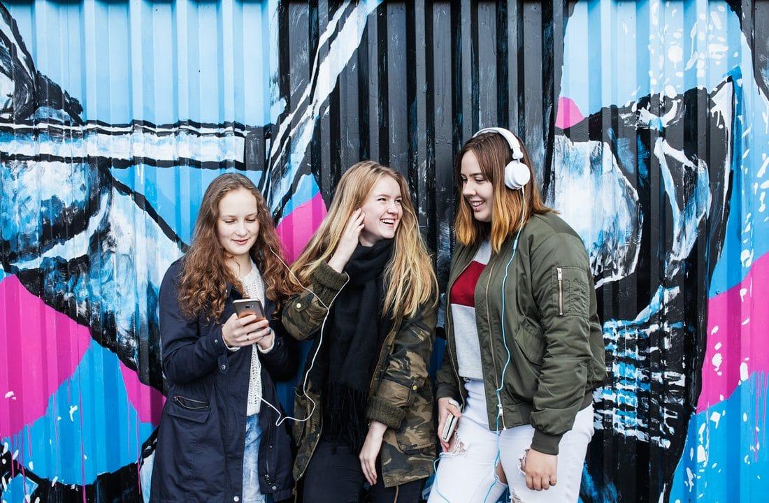 Kolme nuorta tyttöä nojailee iloisina graffitiseinään ja kuuntelee musiikkia kuulokkeilla puhelimistaan.