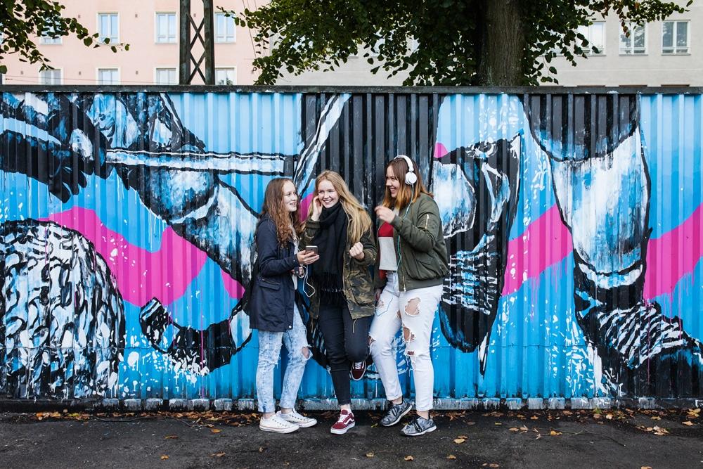 Kolme nuorta tyttö nojailee ulkona graffitiseinään iloisina. He kuuntelevat musiikkia kuulokkeilla puhelimistaan.