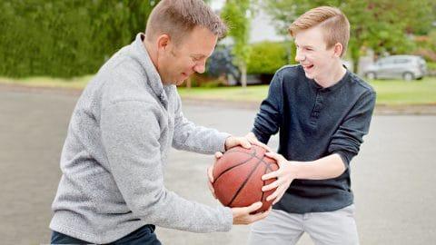 Isä ja poika pelaavat ulkona koripalloa nauraen.