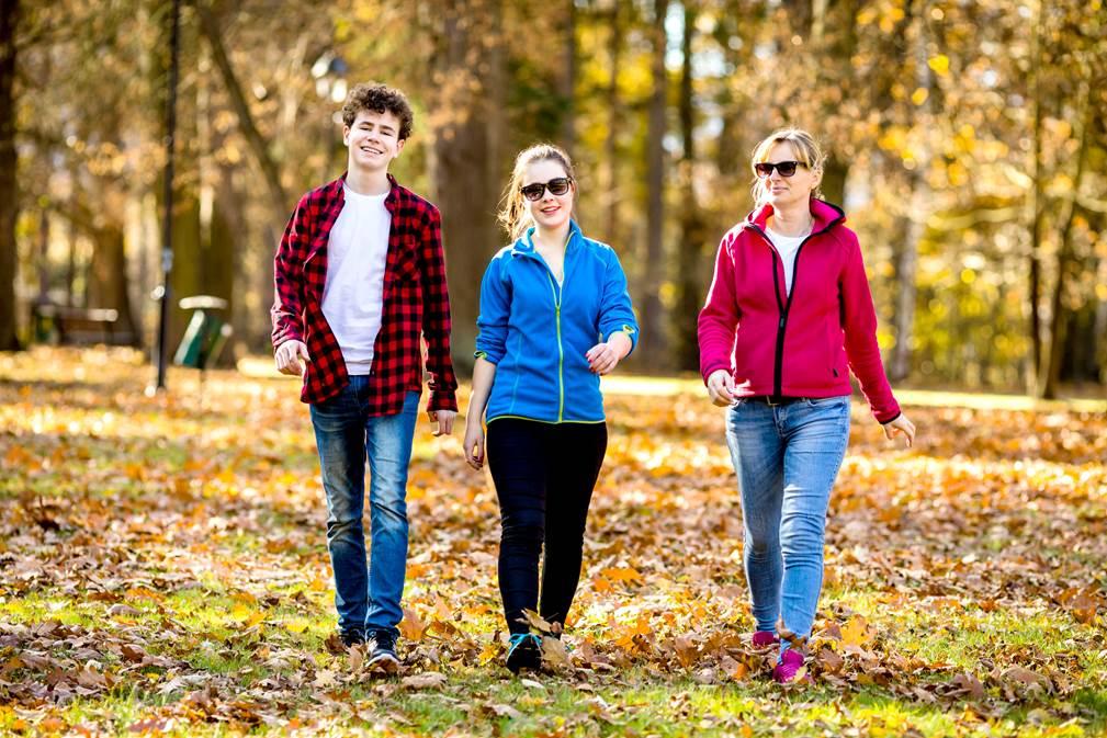 Äiti ja kaksi nuorta kävelee syksyisessä luonnossa.